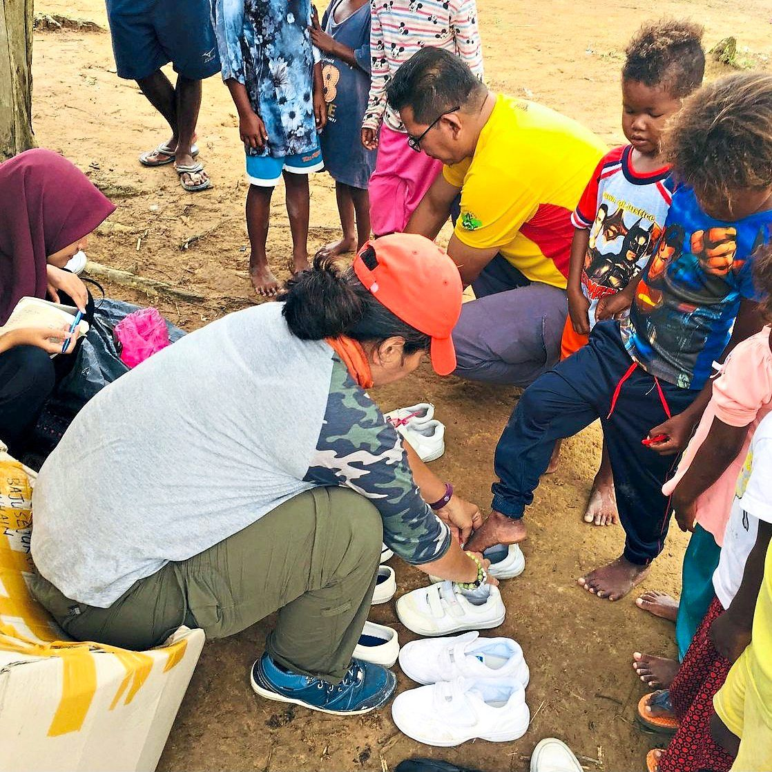 Enaz (in white) collected preloved school shoes for the Orang Asli children at Kampung TanHain in Royal Belum State Park, Perak, in an earlier project. Photo: Projek Asal