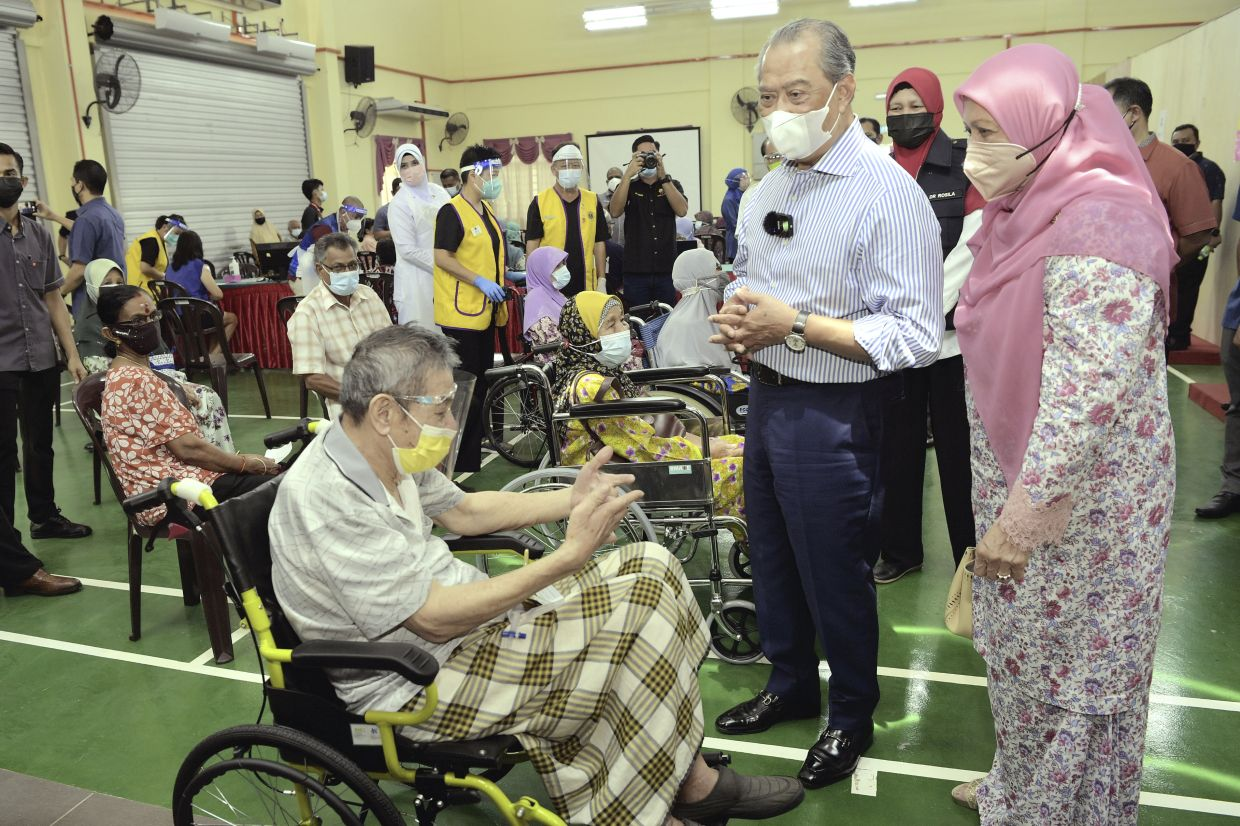 Tan Sri Muhyiddin Yassin (second from right) and his wife Puan Sri Norainee Abdul Rahman (right) talking to an elderly waiting to get vaccinated at PPV Dewan Muafakat Johor Gambir in Tangkak, Johor on June 22. — THOMAS YONG/The Star