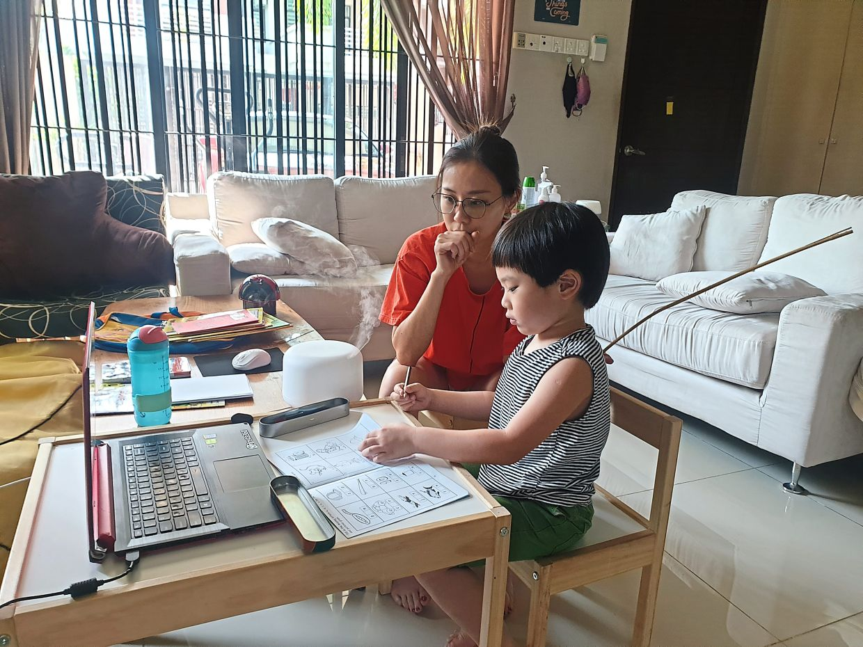 Content creator Hong helping her five-year-old son with his lessons at home.