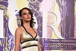 Cara Delevingne has considered a boob job as she thinks her breasts are uneven