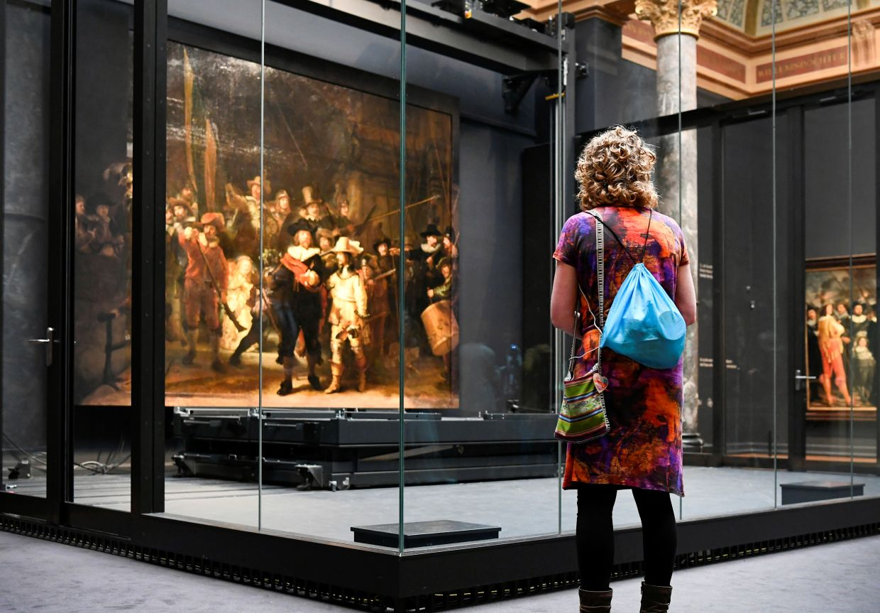A woman looks at Rembrandt's famed 'Night Watch' which is back on display. Photo: Reuters