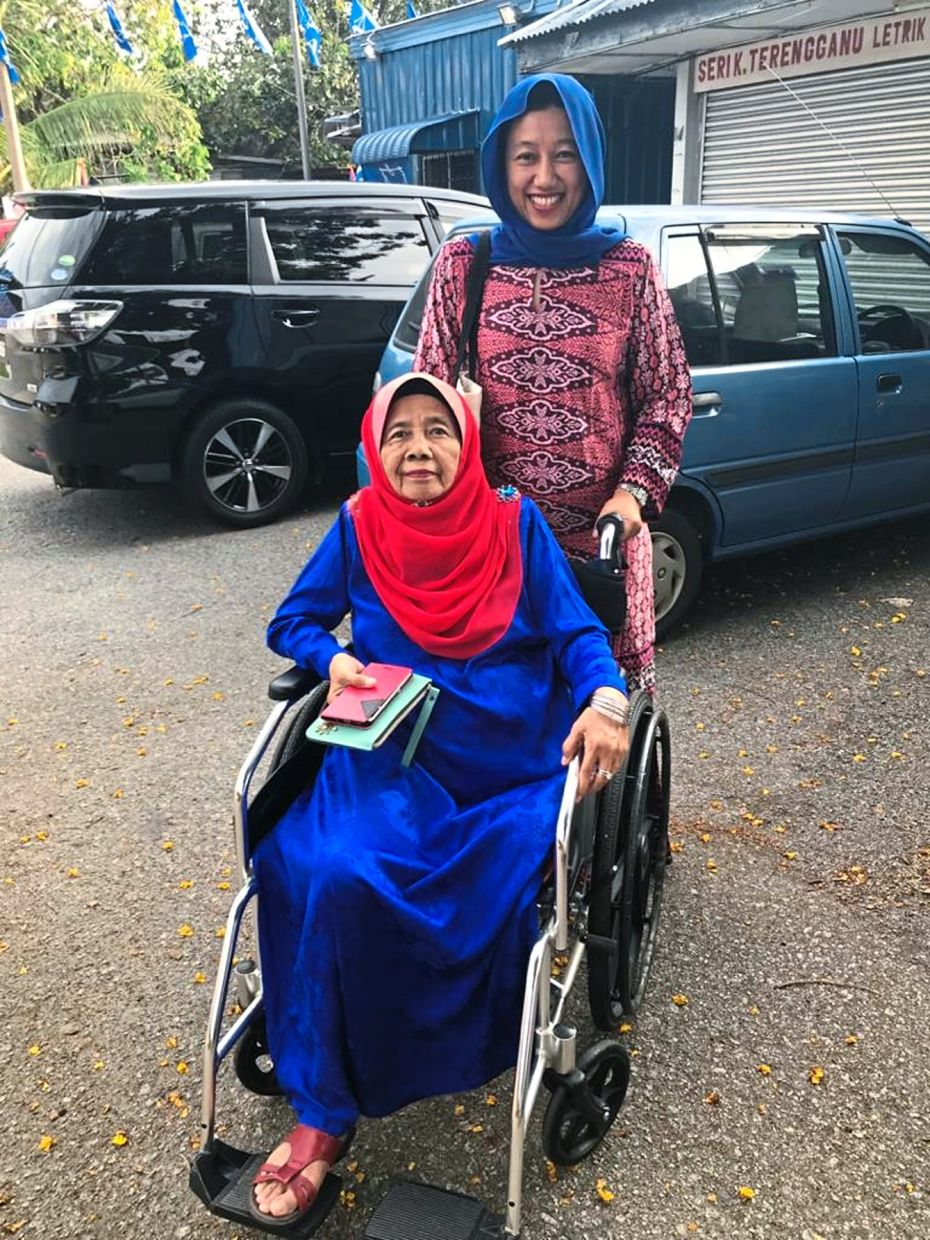 Makcik Ramlah casting her ballot at the 2018 general election, accompanied by her daughter Sheila.