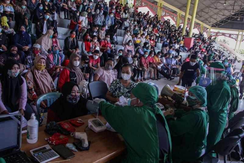 People get medical screening by the health care workers before they receive Covid-19 vaccine during a mass vaccination program at a stadium in Palangka Raya, Central Kalimantan province, Indonesia, on Saturday (June 26, 2021.) - Reuters