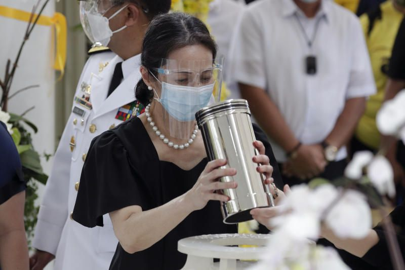 Ballsy Aquino-Cruz holds the urn of her brother former Philippine President Benigno Aquino III before he is placed on the tomb on Saturday, June 26, 2021 at a memorial park in suburban Paranaque city. - AP