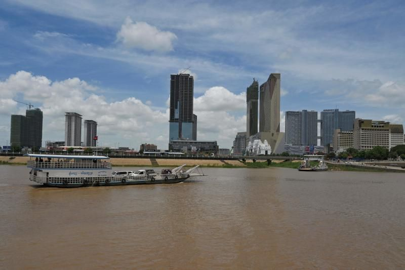 A ferry transporting passengers approaches the jetty along the Mekong River in Phnom Penh with new rows of buildings line the riverbank. - AFP
