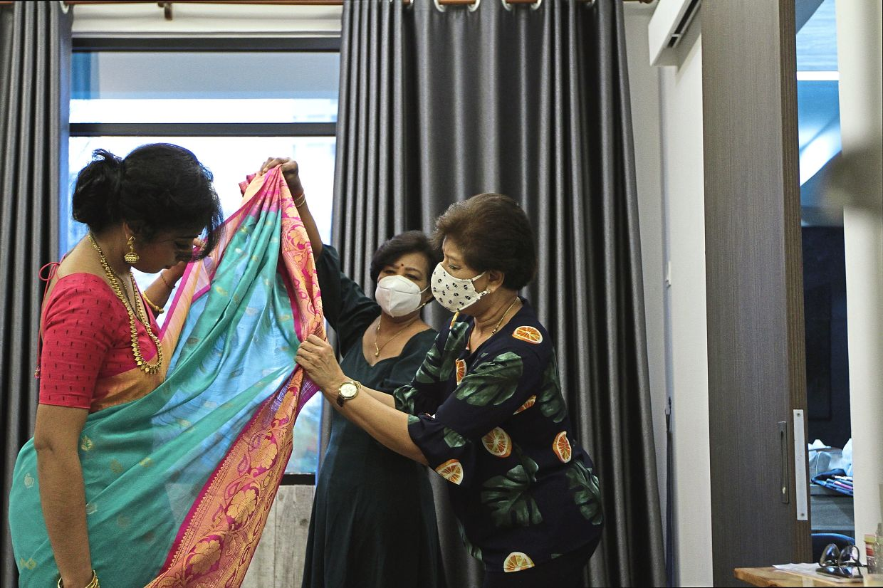 Amu (right) dressing a bride for her big day.