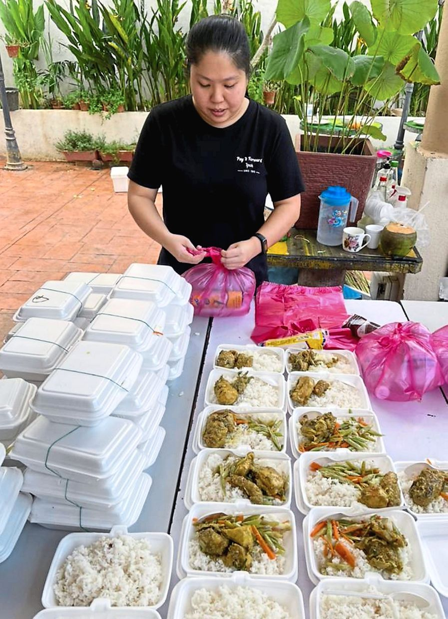 Kind soul: Ho packing the food before distributing it to the homeless  in Ipoh.