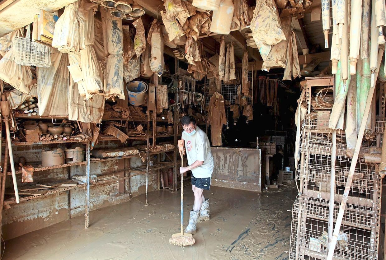 A shop owner cleaning up the mess left by the 2014 floods in Kuala Krai, Kelantan.
