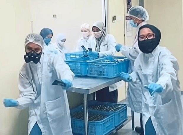 Alam and Nurul Alisya in full PPE suits dancing in a cosmetic products factory for a commissioned gig.