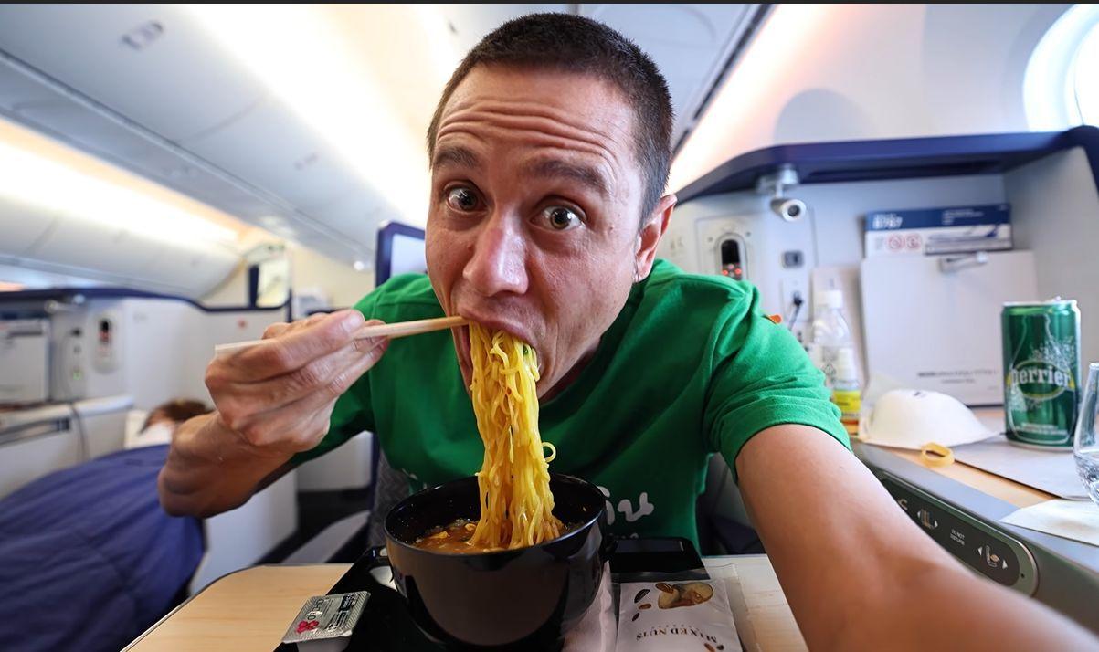 Mark Wiens enjoying a bowl of ramen on his recent flight from Bangkok to Los Angeles.