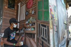 Watch: how artist wraps 'kampung house' mural around boring concrete walls