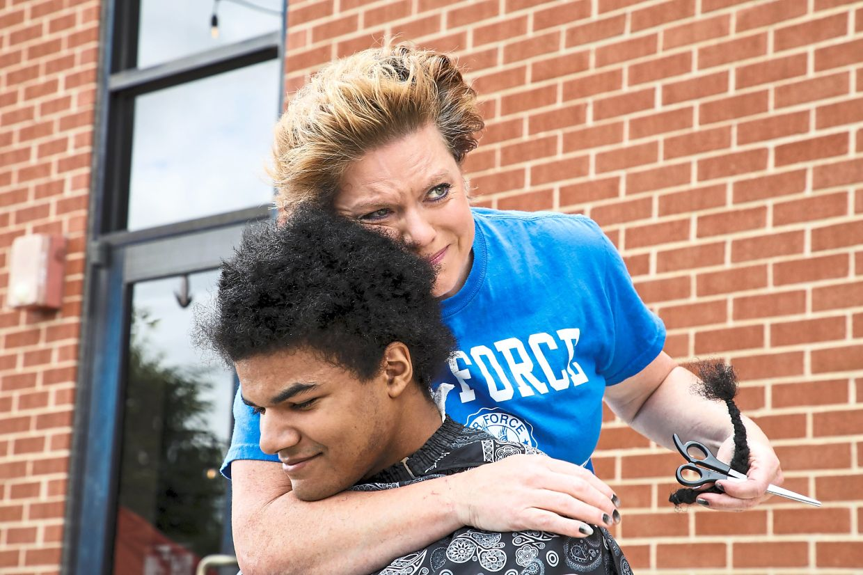 Kelly Moise hugging her son Kieran after cutting the last braid from his hair during a live donation fundraiser, Kieran's Curls for Cancer, for the nonprofit Children with Hair Loss.