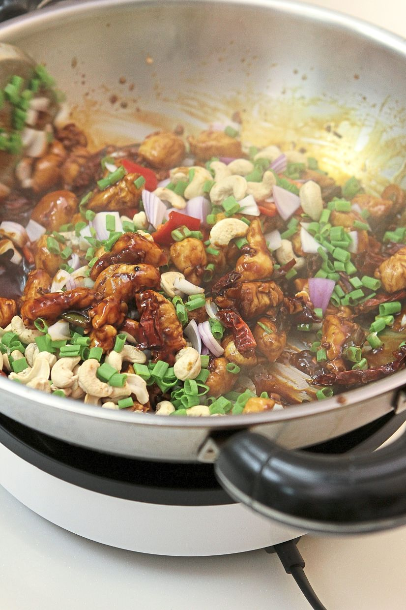Toss in fresh red chilli, spring onion greens and cashew nuts to coat in the gravy just before serving.