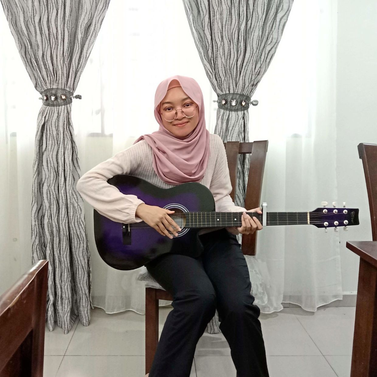 Strumming up harmony: The soothing effects of music helps carry Nur Alia through her solitude.