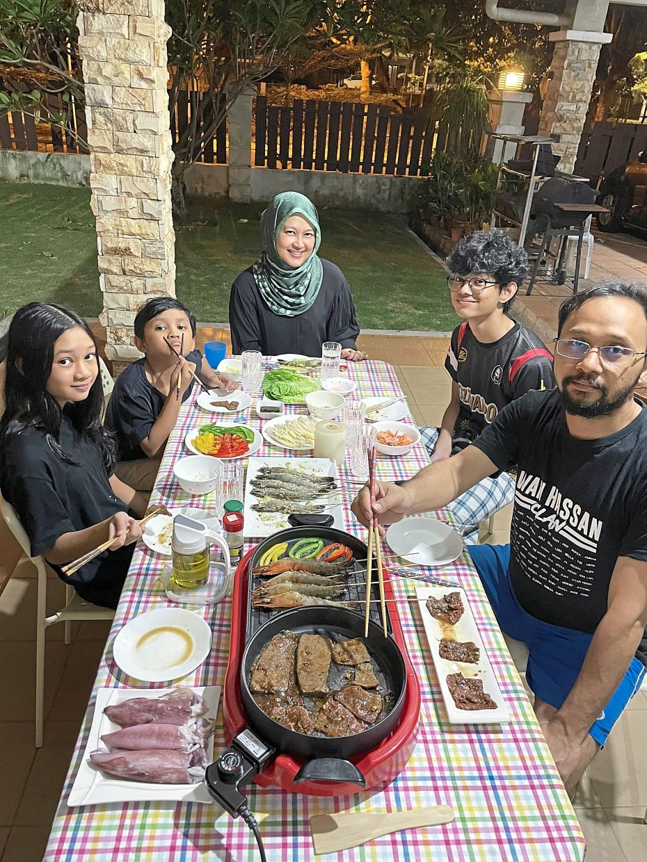 Aliza (centre) and her family have discovered the importance of everyone cooking together and bonding over family meals during the lockdown, when there is little else to do and tempers can flare. — ALIZA HILYATI WAN HARON