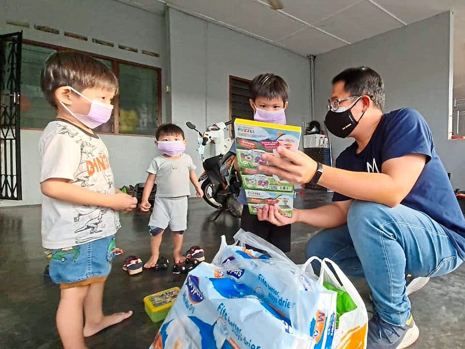 Ling handing over some face masks, diapers, milk powder and foodstuff to a family of five in Yong Peng.