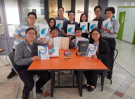 Dr Sim (far left, seated) and Tan (far right, seated) along with their engineering students each holding a copy of their TRIZ program.