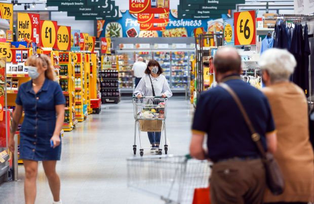 Customers move through a Morrisons supermarket, operated by Wm Morrison Supermarkets Plc, in Saint Ives, U.K., on Monday, July 5, 2021. Apollo Global Management Inc. said Monday it's considering an offer for Morrison, heating up a takeover battle for the U.K. grocer. Photographer: Chris Ratcliffe/Bloomberg