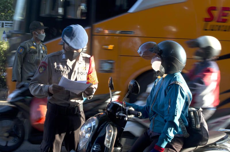 A police officer checks a motorcyclist at a check point during the imposition of an emergency restriction to curb the spread of coronavirus outbreak in Denpasar, Bali, Indonesia on Saturday, July 10, 2021. - AP
