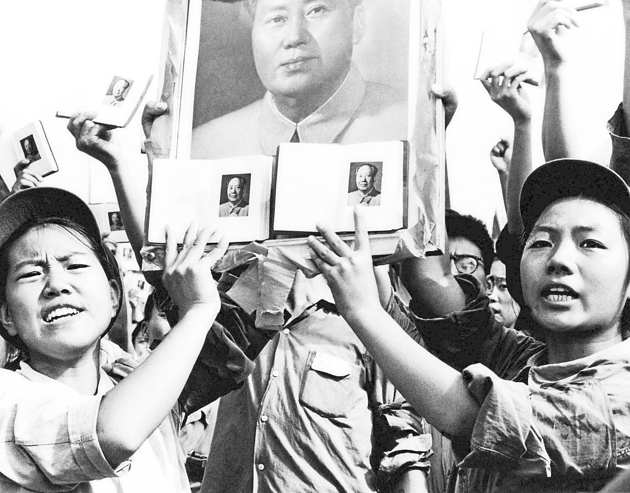 Today's Gen Z in China are harking back to the feelings a much older generation had for Mao. In this 1966 file photo, portraits of the Great Leader and books are being held up at a public rally in Beijing. — AP
