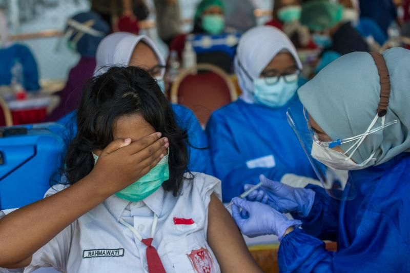 A pupil receives the Sinovac Covid-19 coronavirus vaccine during a vaccination drive for schoolchildren aged 12-18 in Surabaya on Sunday (July 11, 2021), as Indonesia faces its most serious outbreak driven by the highly infectious Delta variant. - AFP