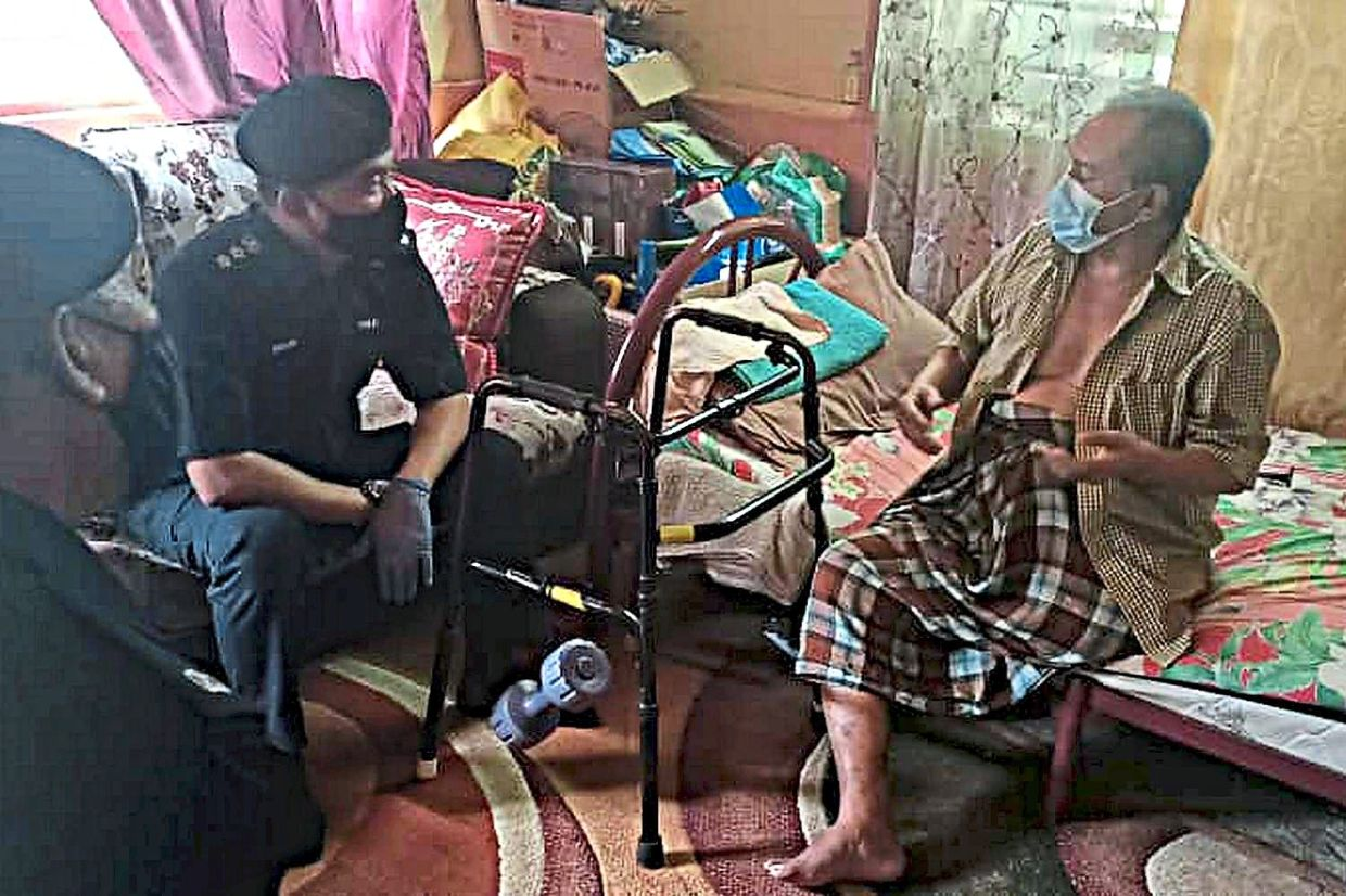 The police speaking to an aid recipient at his home in Bayan Lepas.