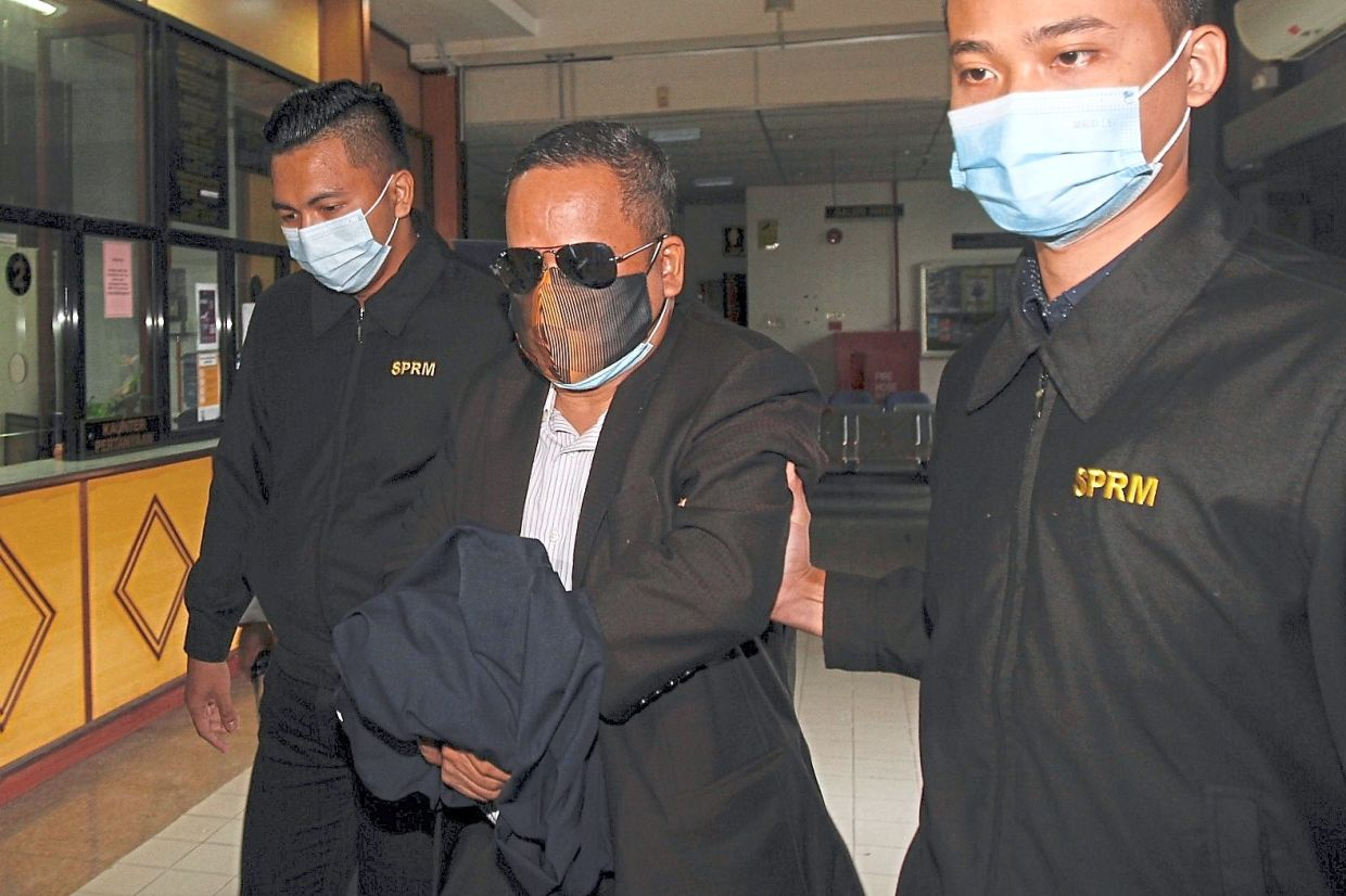 Day in court: Mansor being escorted by MACC officers into the courthouse in Butterworth.