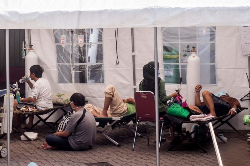Patients receive care underneath a tent, erected on the compounds of a hospital to handle an influx of people suffering from the Covid-19 coronavirus, in Yogyakarta on Monday, July 13, 2021, as Indonesia faces its most serious outbreak driven by the highly infectious Delta variant. - AFP