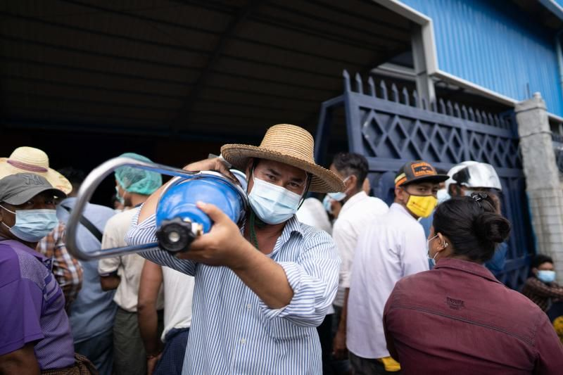 A man carries an oxygen canister, as others wait to fill theirs up, outside a factory in Mandalay on July 13, 2021, amid a surge in Covid-19 coronavirus cases, - AFP