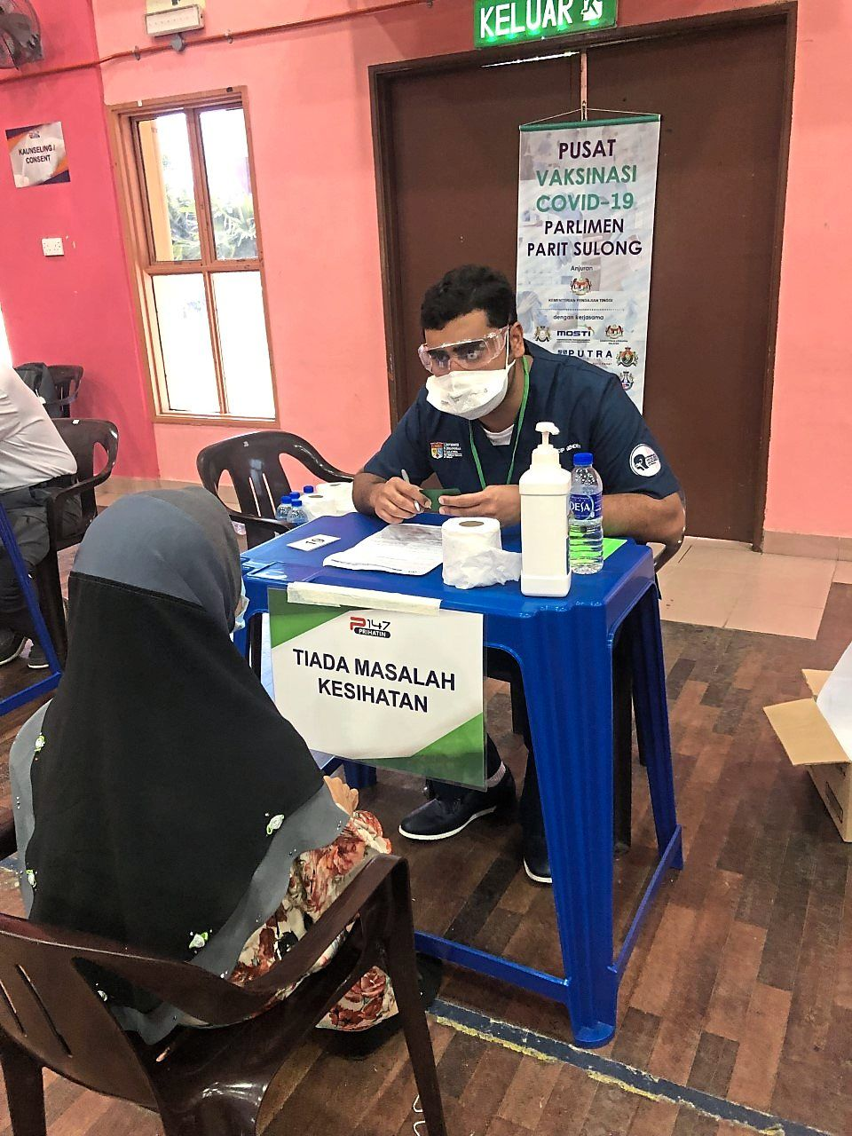 Dr Hardip assesses a woman at the satellite vaccination centre in MRSM Batu Pahat.