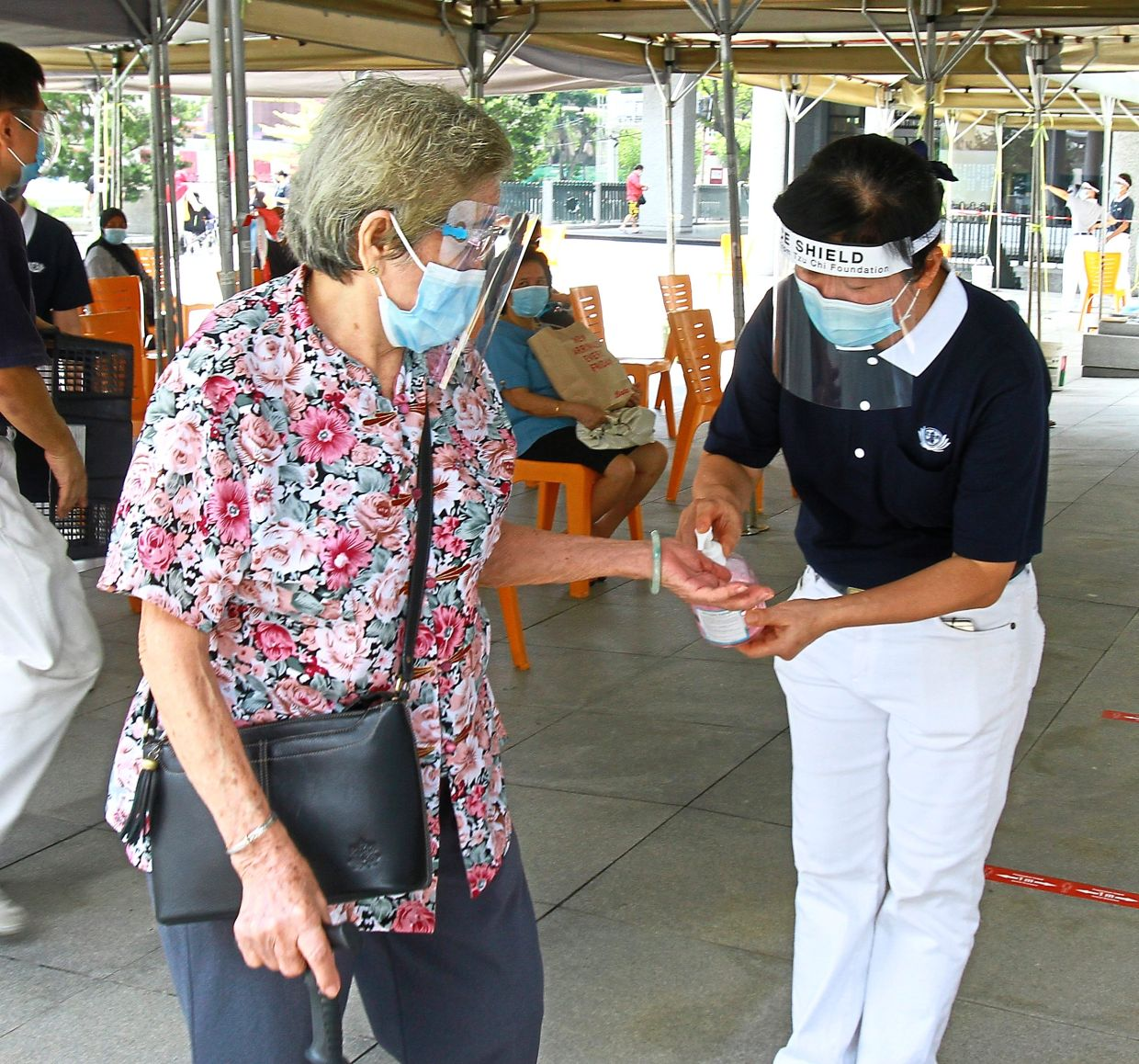 Volunteers stationed at the entrance of the KL Tzu Chi Jing Si Hall in Kepong spraying hand sanitiser on those coming for their vaccines at the Covid-19 vaccination centre. Photo: The Star/Chan Tak Kong
