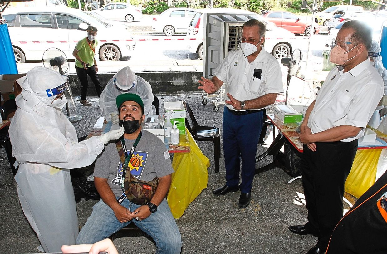 Jagdeep (second right) with state executive councillor Datuk Abdul Halim Hussain (right) observing a swab test in progress at the council market complex in Jalan Rajawali, Bayan Lepas. — ZHAFARAN NASIB/The Star
