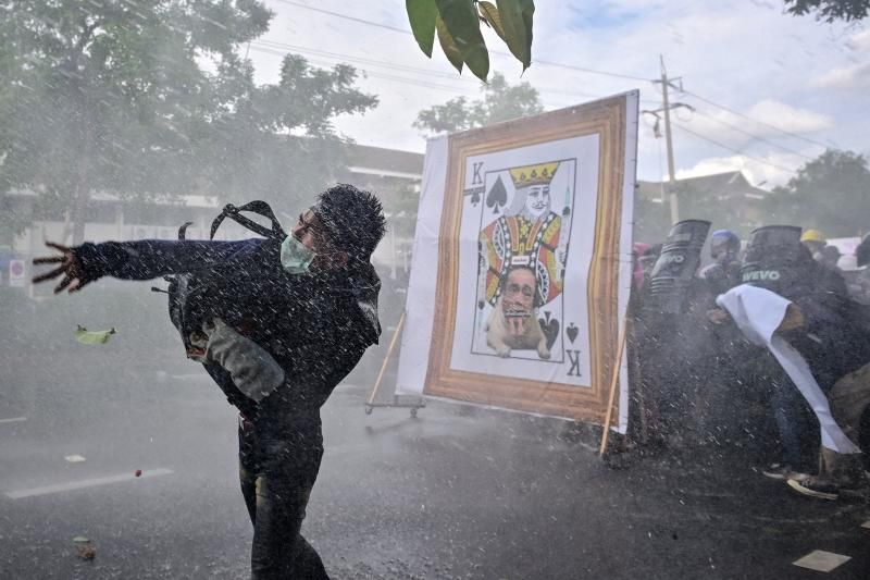 A pro-democracy protester throws an object as others take cover from police water cannon behind a derogatory image of Thailand's Prime Minister Prayut-Chan-O-Cha, as they march to Government House to call for his resignation in Bangkok on Sunday (July 18, 2021). - AFP