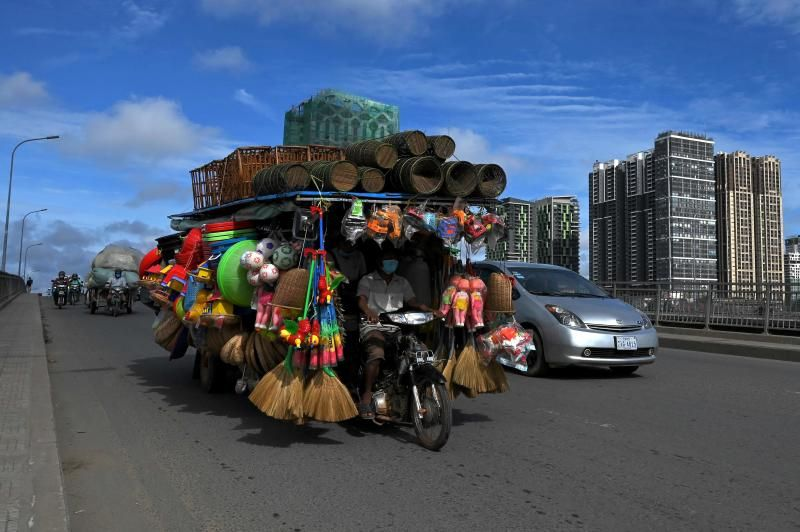 A man rides a motor-cart loaded with goods for sale along a bridge in Phnom Penh. - AFP