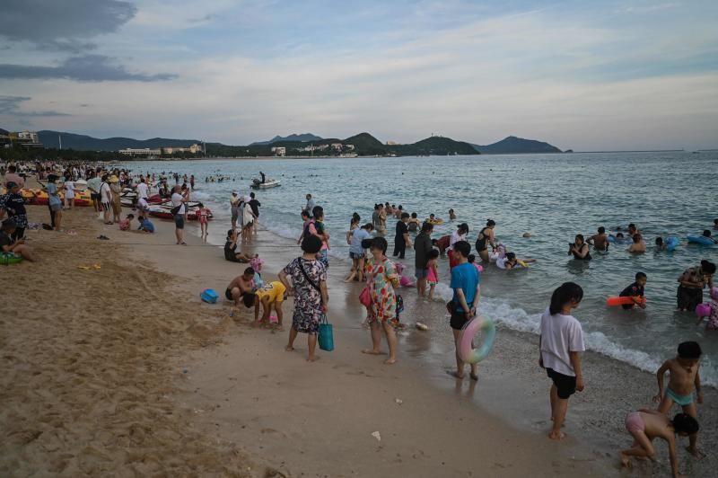 People enjoy bathing at Dadonghai beach in Sanya on China's tropical Hainan Island on Sunday (July 18, 2021). - AFP
