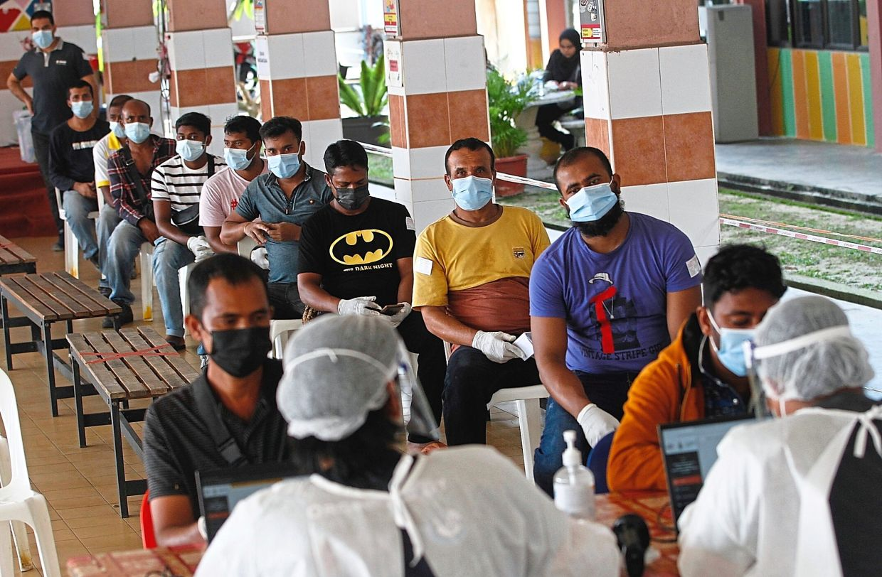 Foreign workers waiting for their Covid-19 swab tests.
