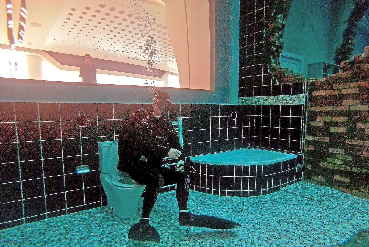 A diver exploring a mock sunken city in the pool.