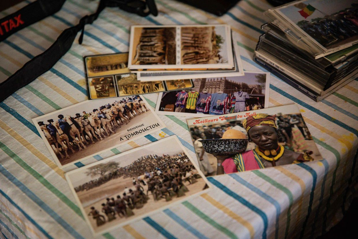Postcards produced by Cisse, known as the initiator of the postcard in Mali, lie on his table in his home in Bamako. Photo: AFP