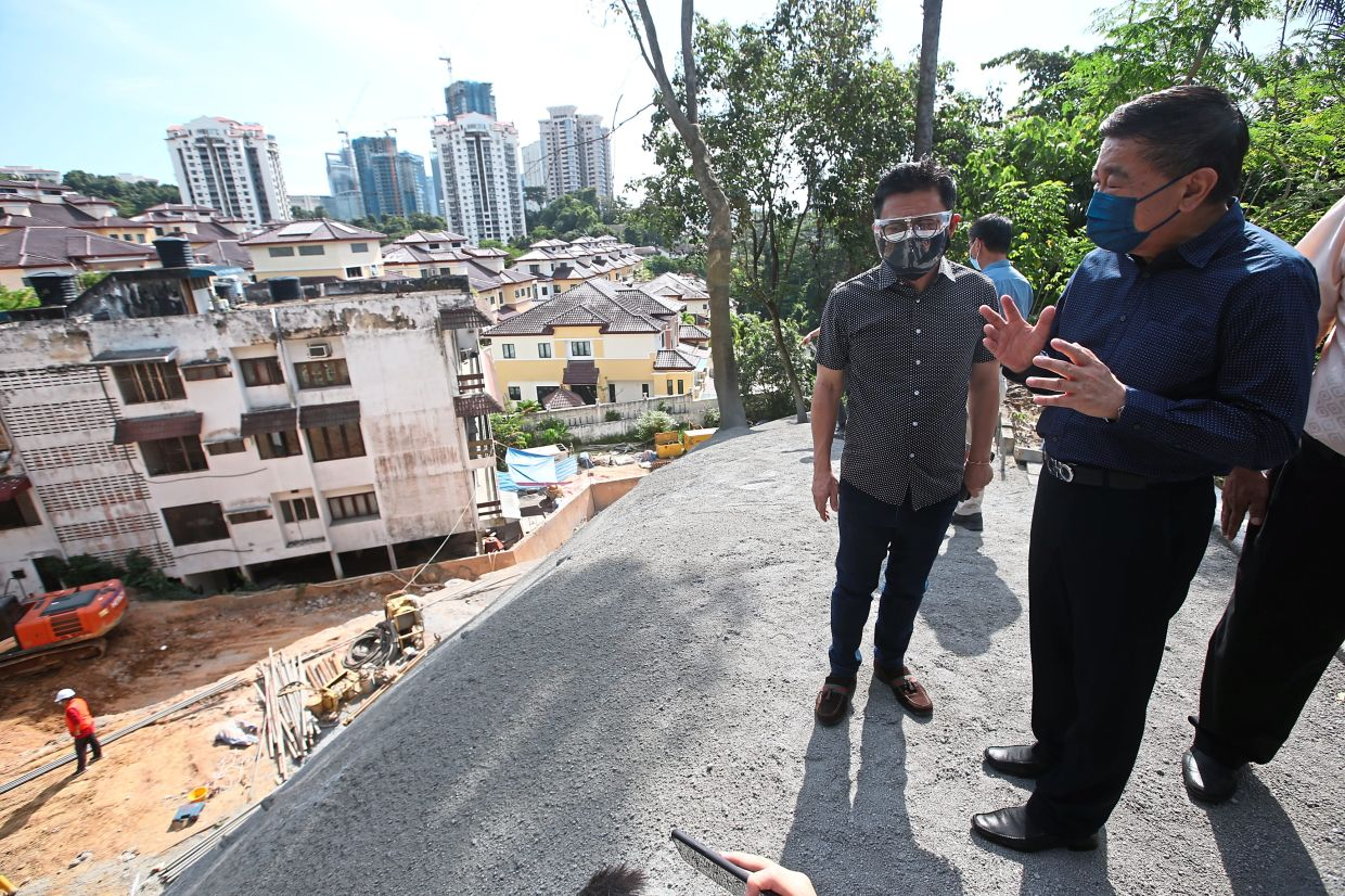 Ti (left) being briefed by Tang at the site.