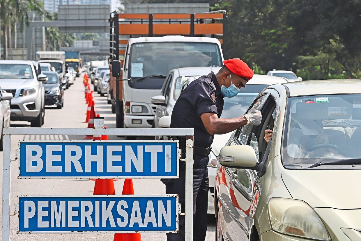 Police personnel checking documents of motorists at a roadblock in Tun Dr Lim Chong Eu Expressway in George Town, Penang. — Filepic