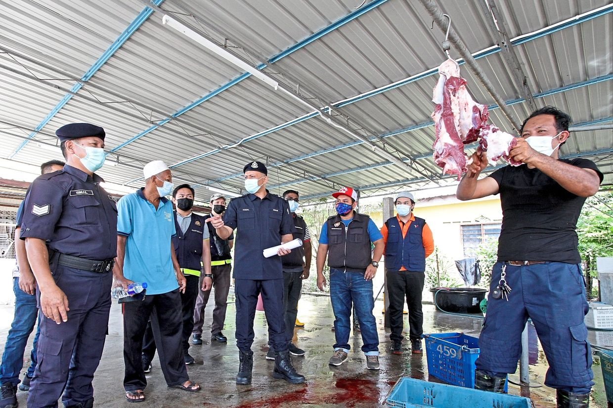 ASP Nor Faizal (third left) leading a team to check on volunteers performing sacrificial rites and the distribution of meat at a mosque in Pajak Song.