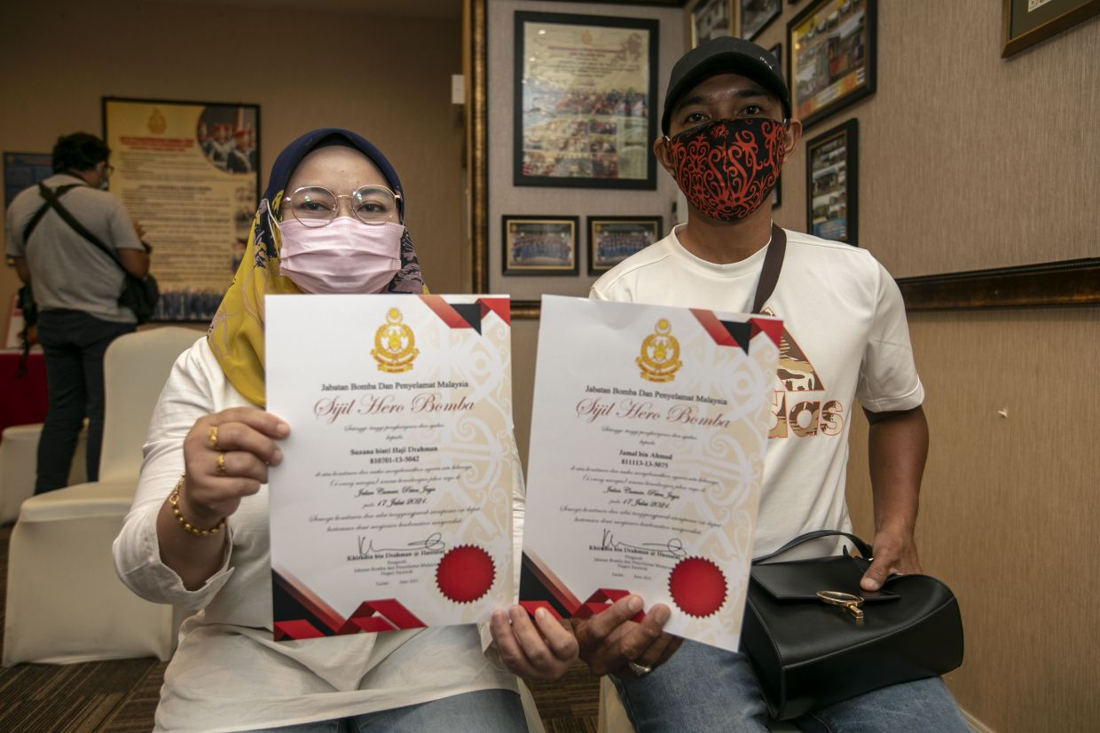 Suzana Drahman and her husband Jamal Ahmad showing their certificates of appreciation from the Fire and Rescue Department.  — ZULAZHAR SHEBLEE/The Star