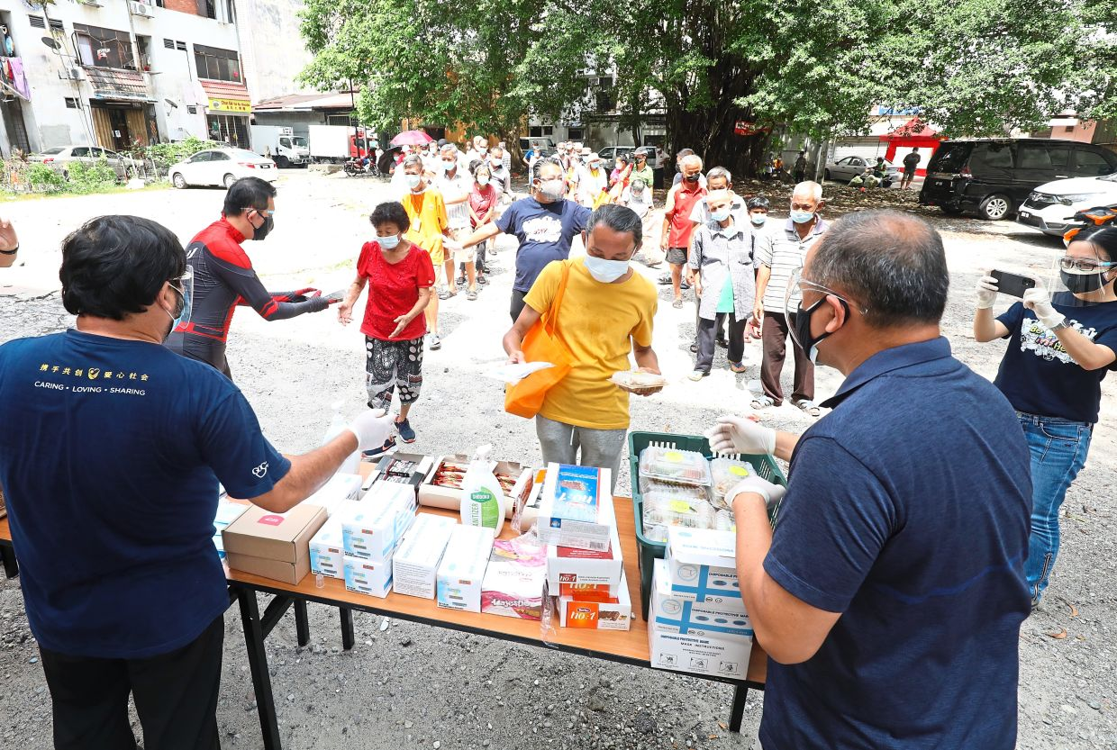 Welcome aid: Ngang (left, in Spider-Man suit) and his team handing out the care packages to the needy in Pudu, Kuala Lumpur. — SAMUEL ONG/The Star