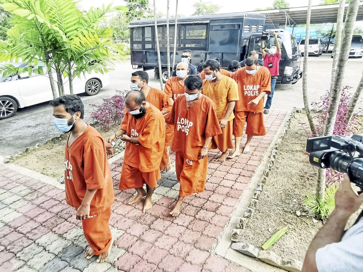 Under investigation: Residents of Taman Pelangi who allegedly participated in a mass congregation on Hari Raya Haji being led in to be remanded at Bukit Mertajam courthouse in Bukit Mertajam, Penang. — LO TERN CHERN/The Star