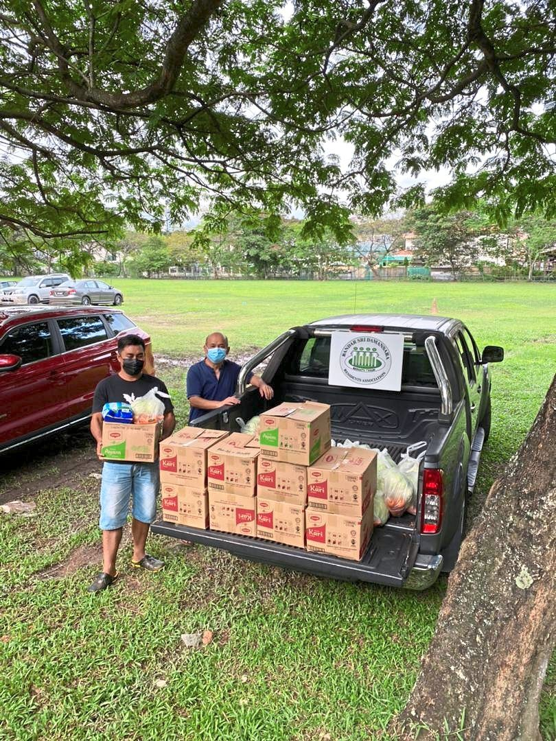 BSDRA committee members distributing essential food items sponsored by businesses and donors under its food aid initiative.