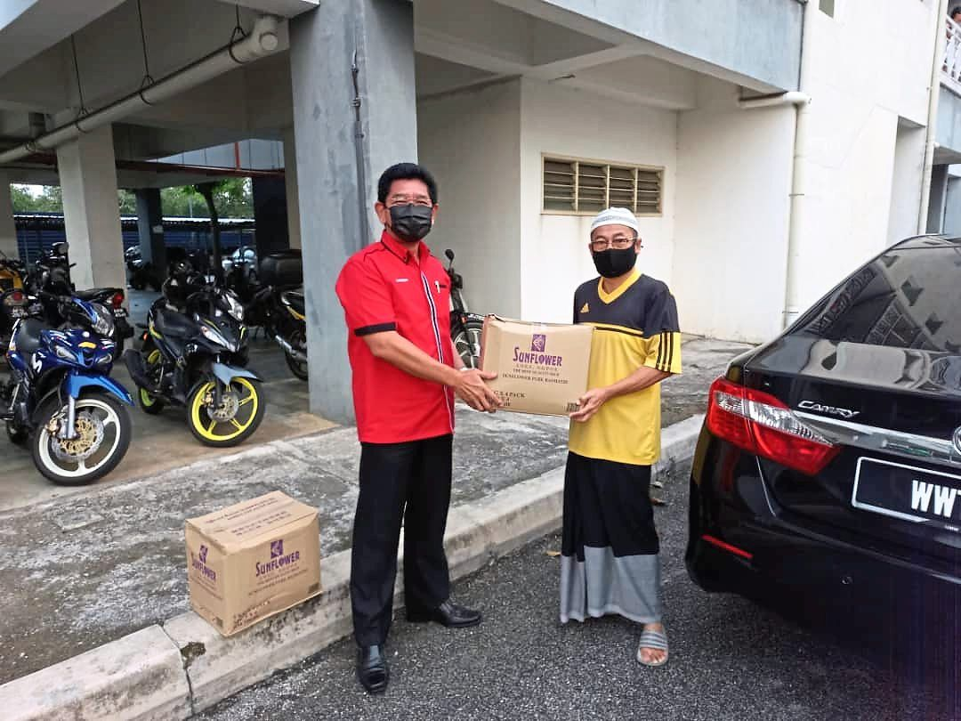 Zainuddin (left) giving a food basket to a recipient who is also a Taman Puncak Jalil resident.
