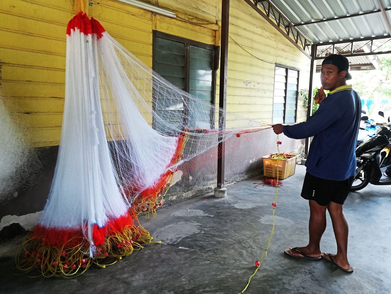 Shalan helps to make new nets for the fishermen. Photo: Dr Serina Rahman