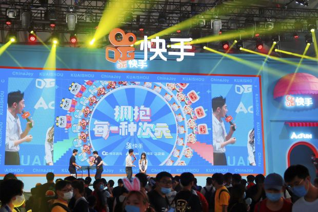 In this July 31, 2020, photo, people watch a performance presented by Chinese technology firm Kuaishou at the ChinaJoy expo in Shanghai.