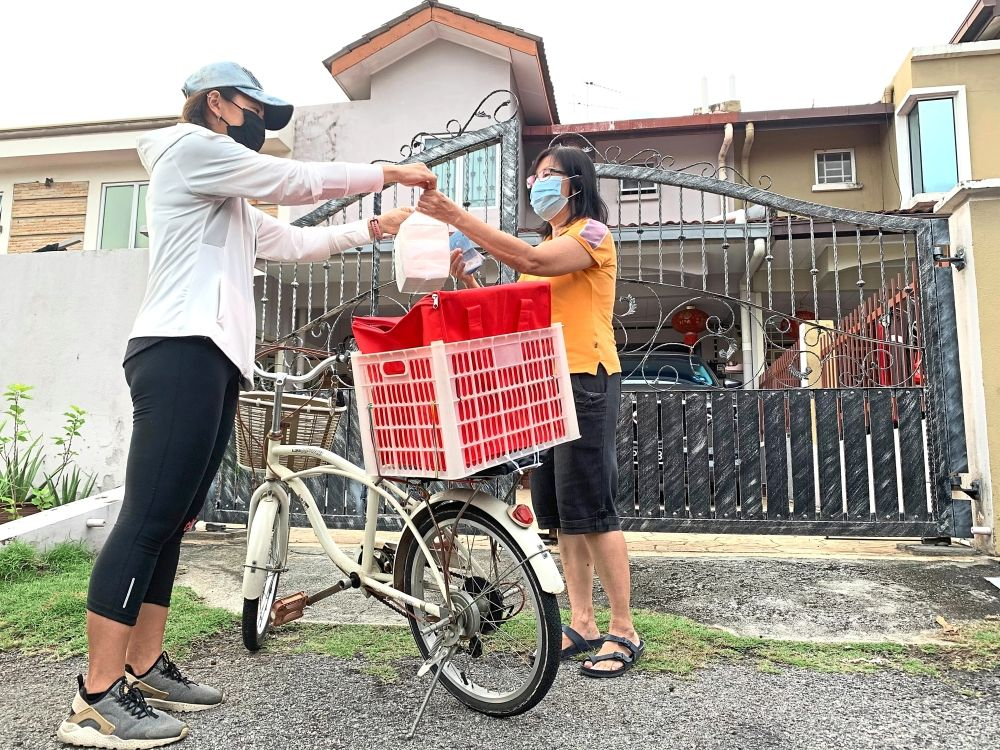 Fast delivery: Winnie Yap Pui Lian (left) delivering an order to May Lee in Taman Puchong Utama 1. The order was placed via a chat group set up to aid entrepreneurs in the neighbourhood and help residents stay home as much as possible. — SS KANESAN/The Star