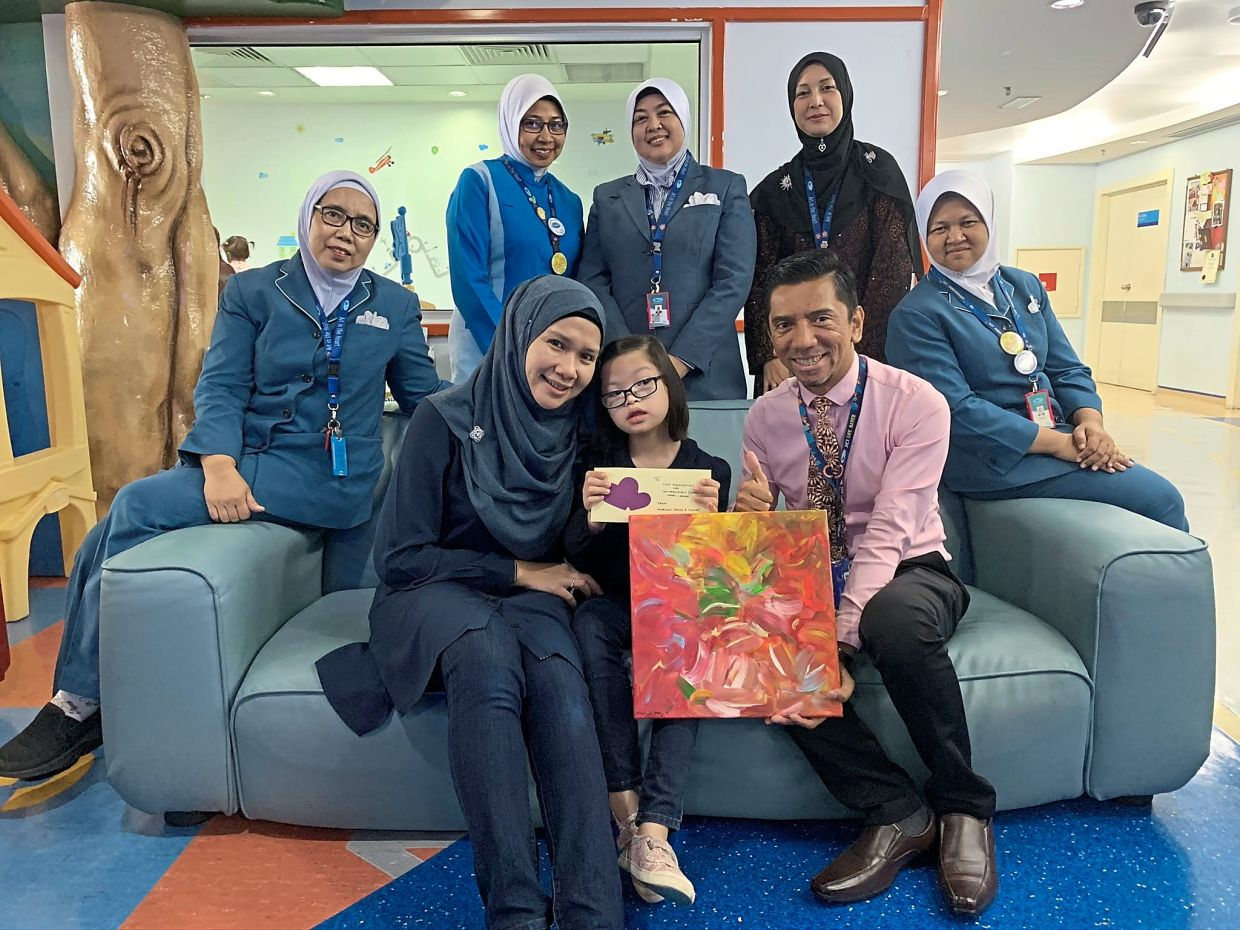 Institut Jantung Negara's Dr Marhisham Che Mood (right, seated) receiving Maryam's painting and donation to aid children in need of heart surgery.